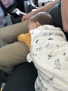 Toddler sleeping on a plane in his sleep sack