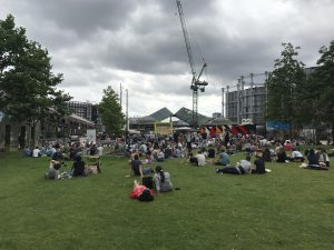 Image of a field with lots of people gathered to watch a screen. Wimbledon is showing.