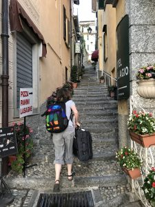 Best things to do in Bellagio, Italy - walk around and explore all the picturesque alleyways. Image of a staircase in an alleyway between two buildings
