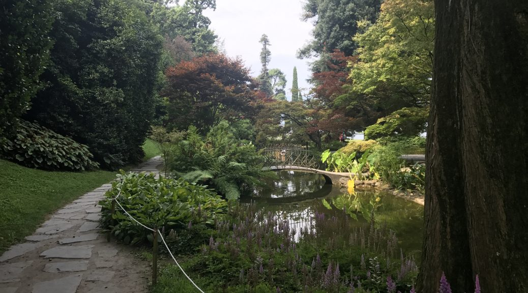 Best things to do in Bellagio: Visit the Giardini Di Villa Melzi. Image of a beautiful pond with green water and lots of different coloured trees surrounding it