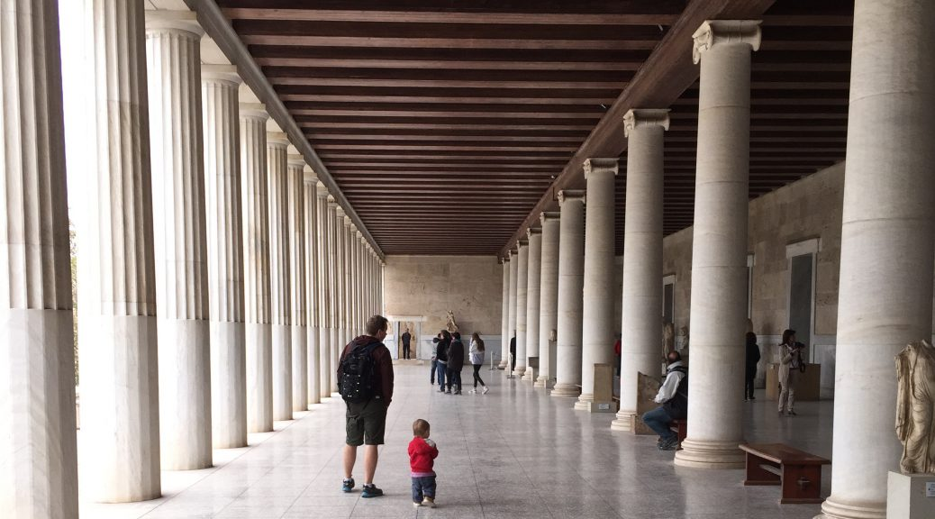 Image of a walkway with a row of columns on each side. In the centre there is an adult and a small boy shown from behind.