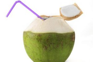 Image of a young coconut with the top cut off and a straw