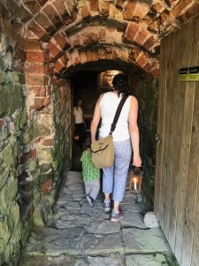 Image from behind of a woman holding a small child's hand and holding a lantern in the other. They're walking into a stone corridor.