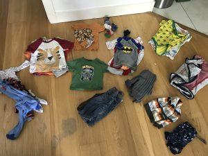 Image of piles of children's clothes sorted by type