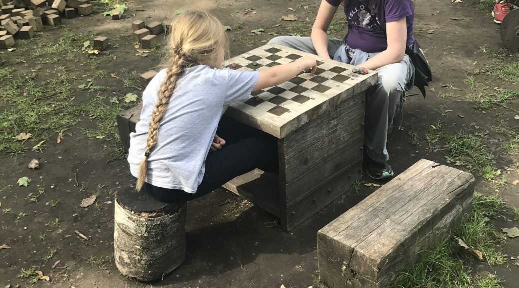 Image of two people sitting at a checkers board