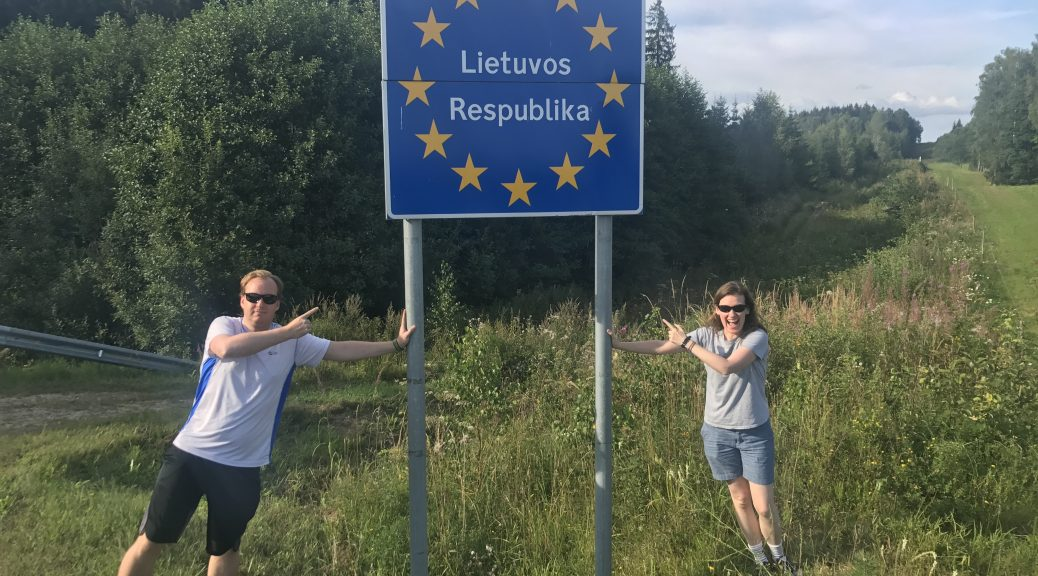 Image of a signpost for the Republic of Lithuania, with two people, one on either side.