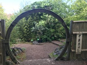 Image of a circular doorway leading into some gardens