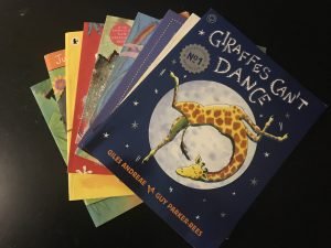 Image of books with 'Giraffes can't dance' on top to help survive a long haul flight with toddler