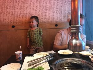 Small boy standing up at the table at the Korean BBQ