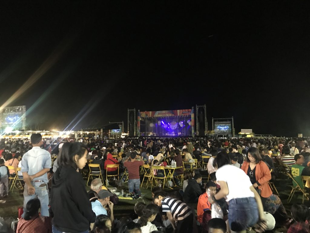 Image of a stage at night time with crowds of people in front