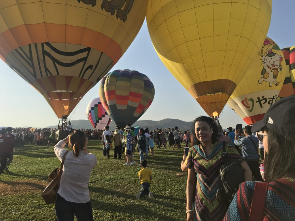Huge hot air balloons on the ground with balloons touching with loads of people around