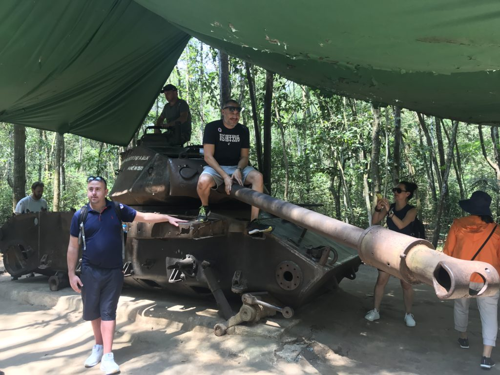 American tourists posing on a tank